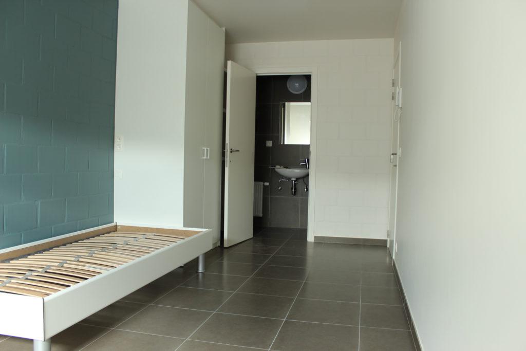Wilgenstraat 45 - Kamer 23 - Bed, kast, deur badkamer met lavabo en deur kamer